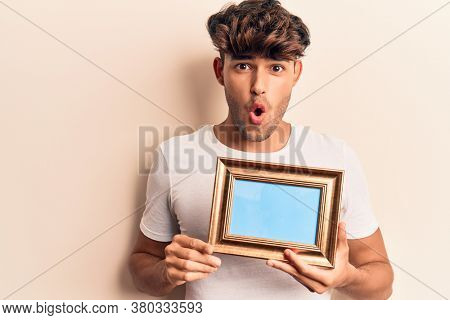 Young hispanic man holding empty frame scared and amazed with open mouth for surprise, disbelief face