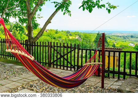 Multi Colored Hammock Made From Strong Fabric Is Hanging On Ropes View On Hilly Landscape.