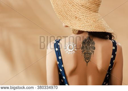 Woman In Polka Dot Swimsuit And Straw Hat With Drawn Sun And Tattoo On Back On Beige Background