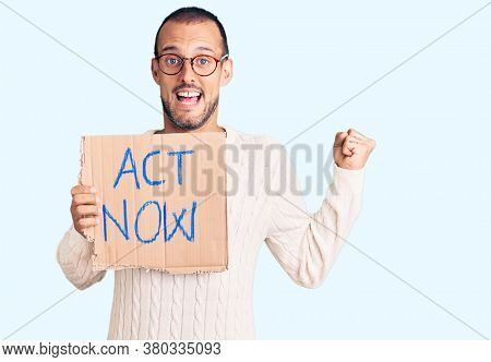 Young handsome man holding act now banner screaming proud, celebrating victory and success very excited with raised arms