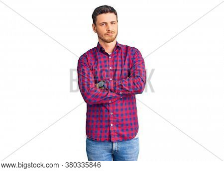 Handsome young man with bear wearing casual shirt skeptic and nervous, disapproving expression on face with crossed arms. negative person.