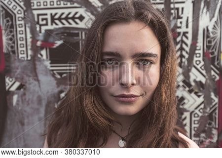 Portrait Of A Young Smiling Woman In Front Of A Wall With Torn Posters