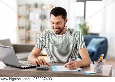 remote job and business concept - happy smiling man with papers, calculator and laptop computer working at home office