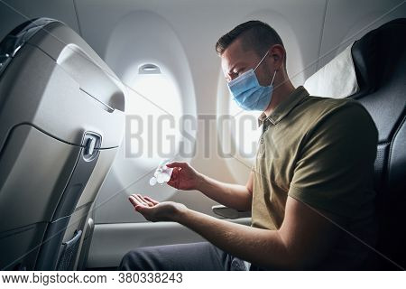 Man Wearing Face Mask And Using Hand Sanitizer Inside Airplane During Flight. Themes New Normal, Cor