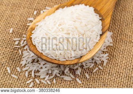 Pile Of Jasmin Rice In A Wooden Spoon On The Sackcloth,