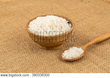 Jasmine Rice In Wooden Bowl And In Wooden Spoon On Sackcloth.