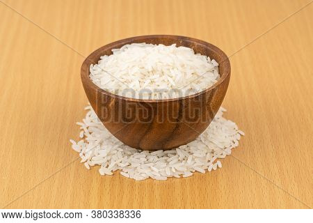 Jusmine Rice In Wooden Bowl On Wooden Table. Rice Is The Most Widely Consumed Staple Food For A Larg