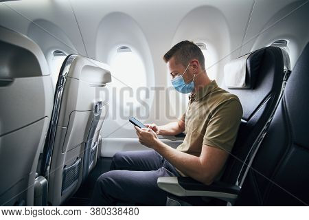 Man Wearing Face Mask And Using Phone Inside Airplane During Flight. Themes New Normal, Coronavirus