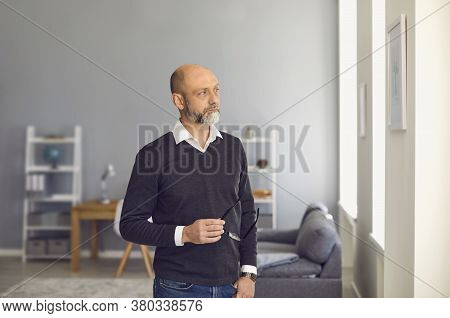 Serious Man Senier With Glasses Standing Looking Away While Standing In A Room At Home.