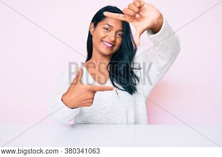 Beautiful latin young woman with long hair wearing casual clothes sitting on the table smiling making frame with hands and fingers with happy face. creativity and photography concept.