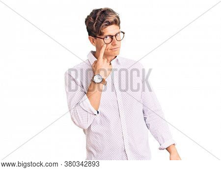 Young handsome man wearing business clothes and glasses pointing to the eye watching you gesture, suspicious expression