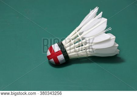 Used Shuttlecock And On Head Painted With England Flag Put Horizontal On Green Floor Of Badminton Co
