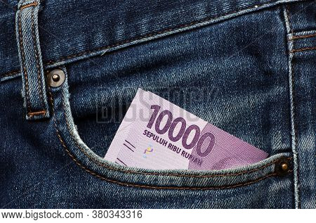 Banknote Money Ten Thousand Indonesia Rupiah In The Pocket Of Blue Jeans. Concept Of Saving Money Or