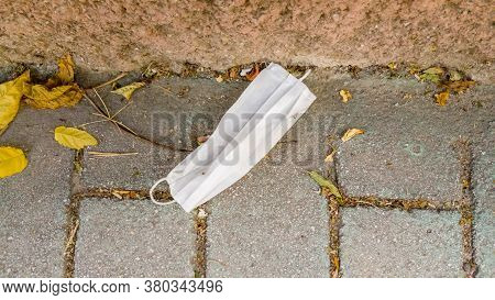 Carelessly Discarded Medical Face Mask Thrown Away On A Sidewalk During Coronavirus (covid-19) Pande