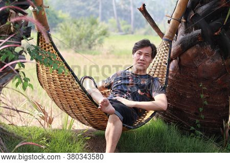 Agriculturist Male Sit Relaxing In The Basketry Crib On The Nature.