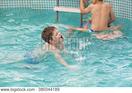 Kids Playing In The Swimming Pool. Leisure And Swimming At Holidays. Prescool Boy Is Having Muscle C