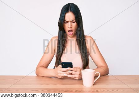 Young caucasian woman sitting at the desk using smartphone drinking coffee scared and amazed with open mouth for surprise, disbelief face