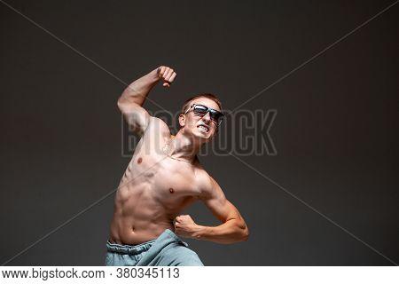 Crazy Young Guy Breakdancer In Sunglasses Dancing Hip-hop Without Shirt In Studio. Dance School Post
