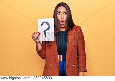 Young beautiful brunette woman holding paper with question mark scared and amazed with open mouth for surprise, disbelief face