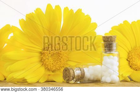 Homeopathic Globules And Glass Bottle Against A Background Of Yellow Flowers Of Calendula, On A Whit