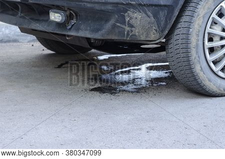 Leakage Of Antifreeze On The Asphalt From Damaged Car. Damage To The Cooling System Due To Road Traf