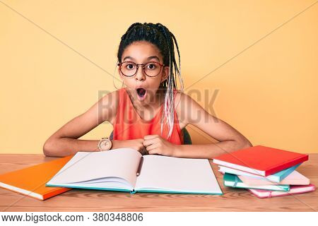 Young african american girl child with braids studying for school exam scared and amazed with open mouth for surprise, disbelief face