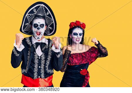 Young couple wearing mexican day of the dead costume over background angry and mad raising fists frustrated and furious while shouting with anger. rage and aggressive concept.