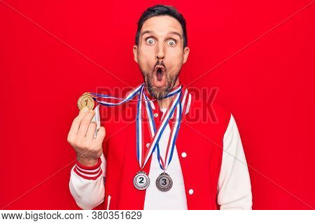 Young handsome sportsman winning medals standing over isolated red background scared and amazed with open mouth for surprise, disbelief face