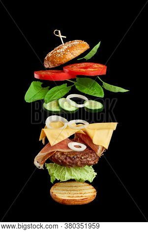 Flying Burger Ingredients: Cutlet, Sesame Seed Bun, Tomato, Onion, Green Lettuce, Cheese On Black Ba