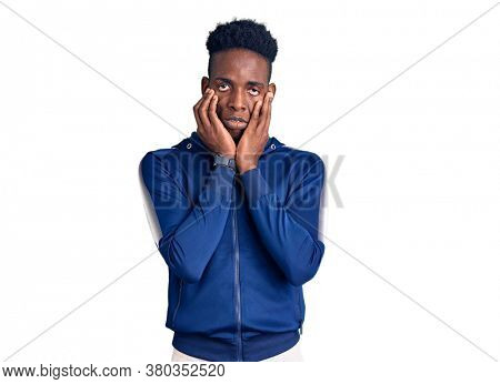 Young african american man wearing sportswear tired hands covering face, depression and sadness, upset and irritated for problem