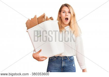 Young beautiful blonde woman holding recycle paper bin scared and amazed with open mouth for surprise, disbelief face