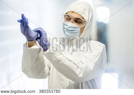 Corona virus concept. Male scientist doctor in mask, glasses and protective suit putting on latex gloves and getting ready for COVID-19 pandemic outbreak quarantine. Man in biochemistry laboratory.