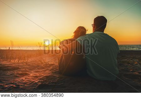Young Lovers Couple Sitting In Sand On Beach At Romantic Golden Sunset. Back View