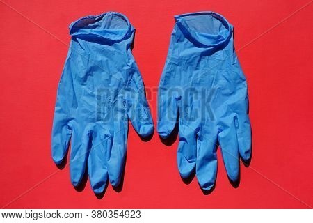 Pair Of Medical Blue Latex Protective Gloves On Red Background. Protective Disposable Gloves Against