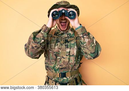 Young caucasian man wearing camouflage army uniform using binoculars angry and mad screaming frustrated and furious, shouting with anger. rage and aggressive concept.