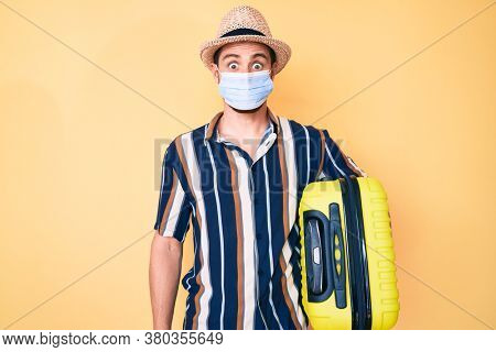 Young handsome man wearing medical mask holding suitcase scared and amazed with open mouth for surprise, disbelief face