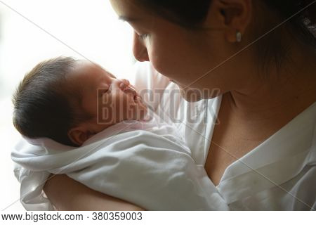 New Born Baby Boy Resting In Mothers Arms.