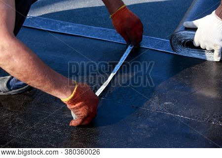 Worker Changes The Line Of Roofing Material