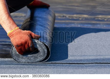 The Worker Puts Roofing Material In The Open Air