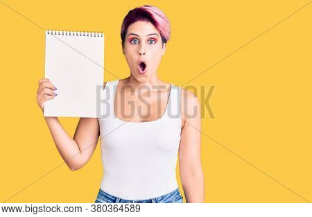 Young beautiful woman with pink hair holding notebook scared and amazed with open mouth for surprise, disbelief face