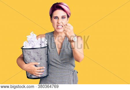 Young beautiful woman with pink hair holding paper bin full of crumpled papers annoyed and frustrated shouting with anger, yelling crazy with anger and hand raised
