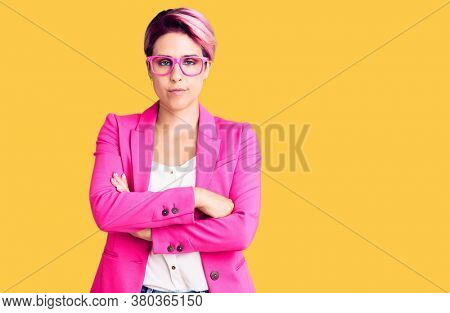Young beautiful woman with pink hair wearing business jacket and glasses skeptic and nervous, disapproving expression on face with crossed arms. negative person.