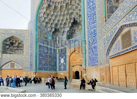 Isfahan, Iran: Many Mem And Women In Traditional Hijabs Walking Near Tile Designed Building In Histo