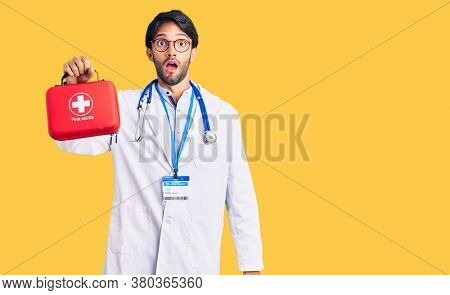 Handsome hispanic man wearing doctor coat holding first aid kit scared and amazed with open mouth for surprise, disbelief face
