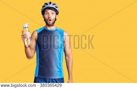 Handsome hispanic man wearing bike helmet and holding water bottle scared and amazed with open mouth for surprise, disbelief face