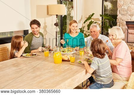 Family of three generations having lunch together at the big dining table