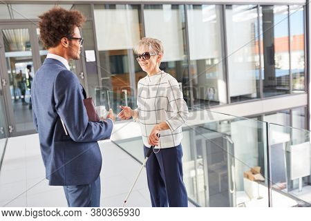 Blind old woman with cane talks to a businessman in the office hallway