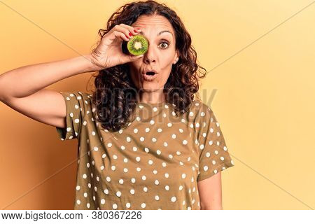 Middle age beautiful woman holding kiwi over eye scared and amazed with open mouth for surprise, disbelief face