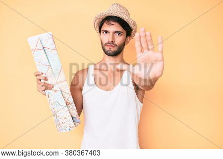 Handsome hispanic man holding city map for summer trip with open hand doing stop sign with serious and confident expression, defense gesture