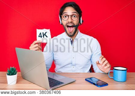 Handsome hispanic man working at the office holding 4k  banner scared and amazed with open mouth for surprise, disbelief face